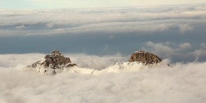 Two mountain peaks coming out of the clouds